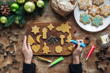 Partial view of woman decorating homemade christmas cookies with food grade ink on wooden surface stock vector