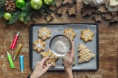 Fotografie partial view of woman pouring sugar powder on christmas cookies on baking pan