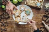 Fotografie částečný pohled muže a ženy drží domácí sušenky na dřevěnou desku s dekorativní vánoční věnec