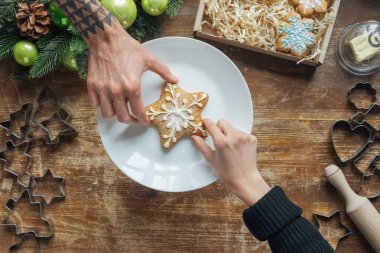 partial view of man and woman holding homemade cookie on wooden tabletop with decorative christmas wreath
