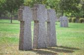 zblízka pohled stejných starých náhrobků v řadě na trávě na hřbitově