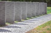 Pamětní náhrobní kameny s nápisy umístěné v řadě na hřbitově