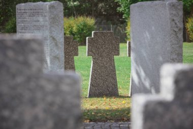 selective focus of memorial stone crosses placed in row at cemetery