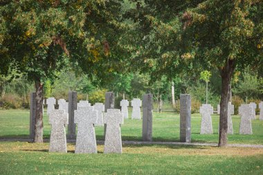 old memorial stone crosses placed in rows at cemetery