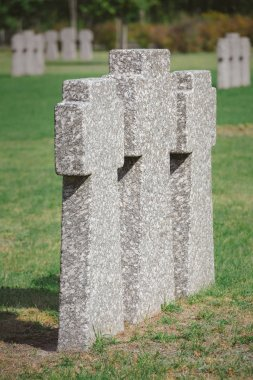 Close up view of identical memorial stone crosses placed in row at cemetery stock vector