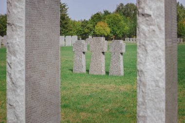 Selective focus of identical memorial stone crosses placed in row at graveyard stock vector