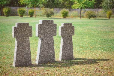 Selective focus of memorial stone crosses placed in row on grass at graveyard stock vector
