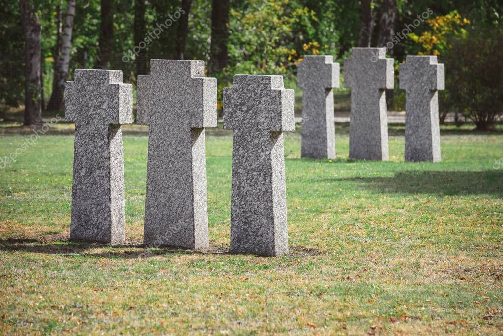 Selective focus of identical gravestones placed in rows at graveyard stock vector