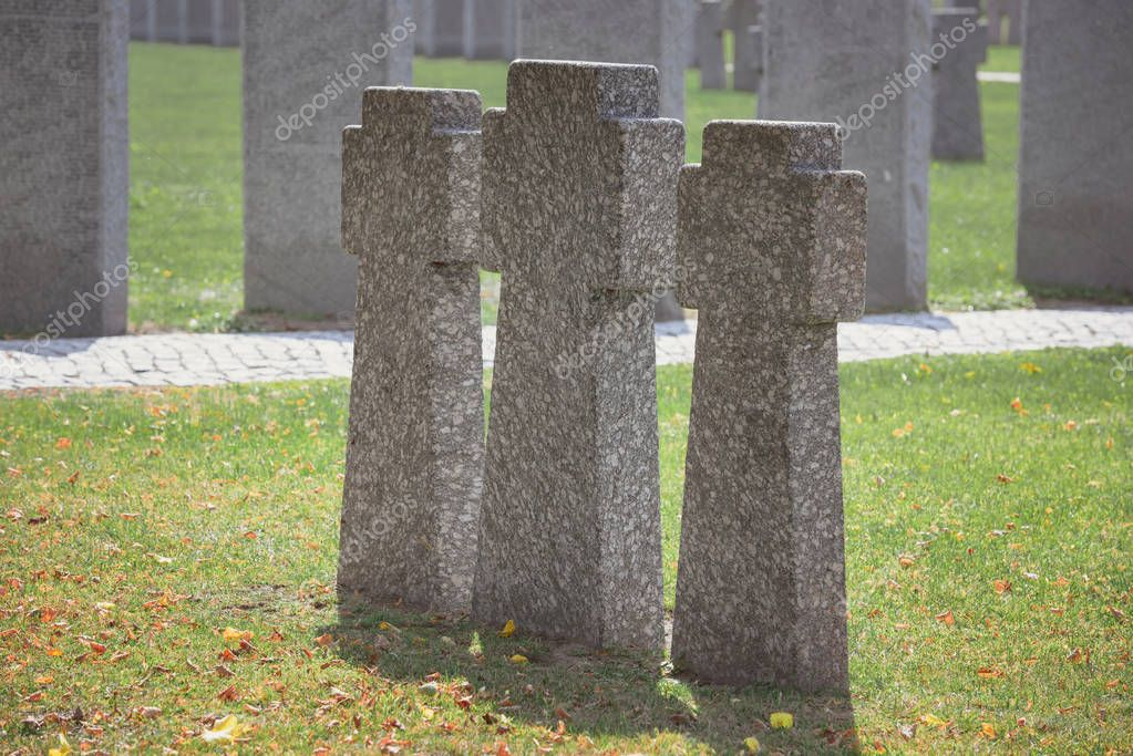Selective focus of identical old memorial headstones placed in row at cemetery stock vector