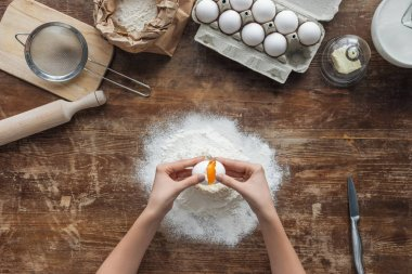 top view of female hands smashing egg in flour on wooden table
