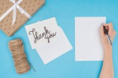 white postcard with thank you lettering and blank sheet isolated on blue background