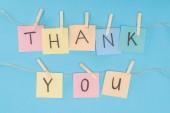 bunte klebrige Notizen Schreibweise Danke auf Spitze mit Wäscheklammern isoliert auf blauem Hintergrund