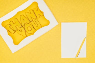 Square-shaped cake in box with thank you lettering and notebook isolated on yellow background stock vector