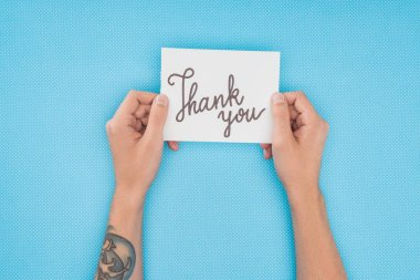 cropped person holding paper with thank you lettering isolated on blue background