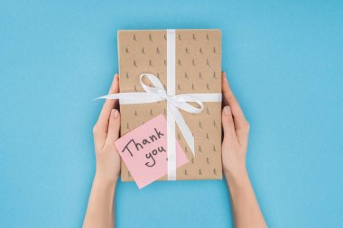Cropped person holding gift box with sticky note with thank you lettering isolated on blue background stock vector