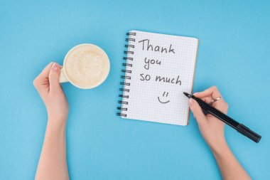 cropped person holding pen and cup of coffee above notebook with thank you so much lettering isolated on blue background