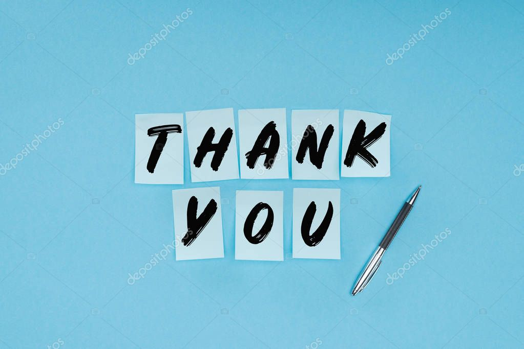 thank you wording on sticky notes and pen isolated on blue background