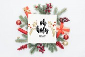 top view of pine tree branches, christmas decorations and gifts  with oh holy night lettering in middle isolated on white