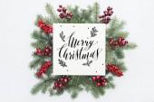 fenyő fa koszorú, karácsonyi díszek, a boldog karácsonyt betűkkel elszigetelt fehér középső felső nézetében