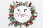 pohled shora z borovice strom věnec s vánoční výzdobou, s nápisem merry christmas uprostřed izolované na bílém