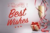 Fotografie Sklenka šampaňského a zabalený dárek na šedém pozadí s Všechno nejlepší a merry christmas písmo