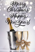 bottle of champagne in bucket and glasses of champagne on grey backdrop with merry christmas and happy new year lettering