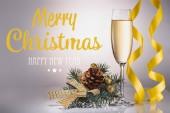 Sklenka šampaňského, Vánoční dekorace a konfety na šedém pozadí s Veselé Vánoce a šťastný nový rok nápisy