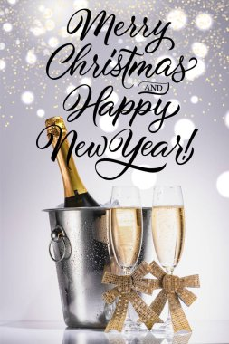 Bottle of champagne in bucket and glasses of champagne on grey backdrop with