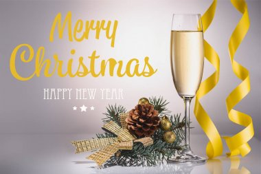 glass of champagne, christmas decoration and confetti on grey backdrop with