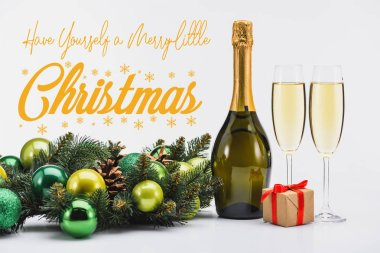 bottle and glasses of champagne, christmas wreath and gift on white background with