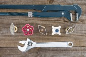 Photo top view of plumber wrenches and various plumbing valves on rustic wooden tabletop