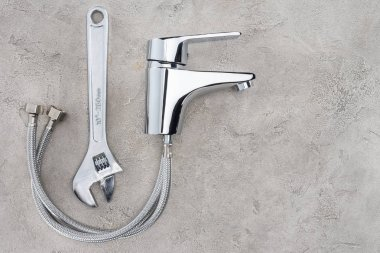 top view of water mixer and pipe wrench on concrete surface