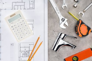 top view of building plan with various tools and calculator on concrete surface