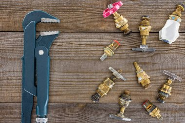 top view of plumber wrench and various plumbing valves on rustic wooden tabletop