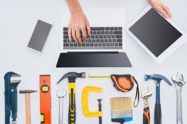 cropped shot of woman using gadgets with various tools lying on white