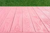 Fényképek rózsaszín fa deszka felülete a zöld fű háttér