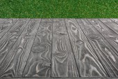 Fotografie  surface of grey wooden planks on green grass background