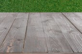 surface of grey wooden planks with green grass on background