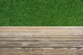Fotografie template of brown wooden floor with green grass on background