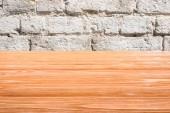 Šablona oranžové dřevěné podlahy s bílým cihlová zeď na pozadí