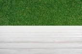 Šablona bílé dřevěné podlahy s trávou na pozadí