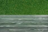 Fotografie Šablona tmavě zelené dřevěné podlahy s trávou na pozadí