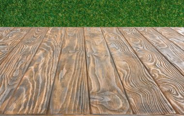 surface of brown wooden planks on green grass background