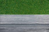 template of grey wooden floor on green grass background