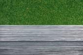 Fotografie template of grey wooden floor on green grass background