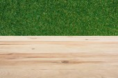 Photo template of beige wooden floor with green grass on background