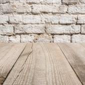 povrch béžové dřevěných prken s s cihlovou zeď v pozadí