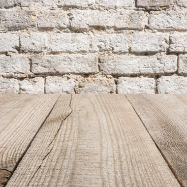 surface of beige wooden planks with with brick wall on background