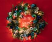 Fotografie pohled shora na vánoční věnec zdobený hračky a světla na červeném pozadí s Vánoce se blíží inspirace