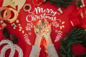 Fotografie oříznutý snímek ženy držící v rukou borové větve a dekorace pro ruční věnec na červené pozadí s nápisem merry christmas vánoční osvětlení